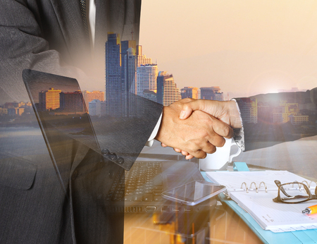 Double exposure of success businessman and Office workplace with laptop and smart phone on wood table and big city blurred background