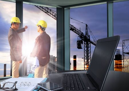 table work at office and  engineering man standing with sunset scene and building construction Silhouette Building background Stockfoto
