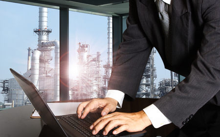 success businessman using computer laptop with oil refinery industry  of heavy industry background