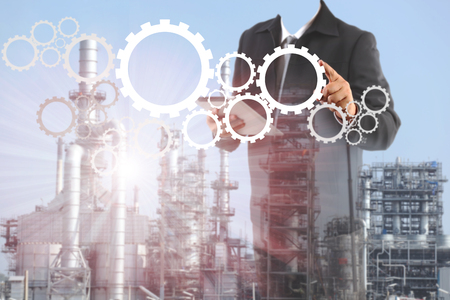 industry background: Double exposure of success businessman using digital tablet with  oil refinery industry in metallic color style use as metal style of heavy industry background Stock Photo