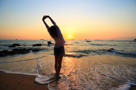 outspread: Enjoyment - free happy woman enjoying sunset. Beautiful woman in white dress embracing the golden sunshine glow of sunset with arms outspread and face raised in sky enjoying peace, serenity in nature Stock Photo