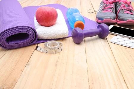 Sport equipment.  water, towel, earphones and phone on wooden background