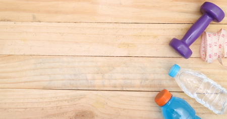 unattached: An apple, a measuring tape and dunbbell on wood Stock Photo