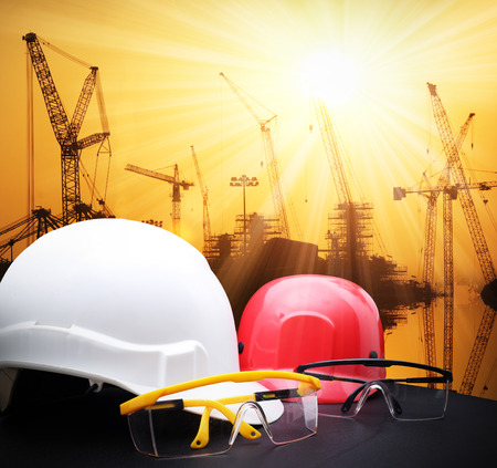 safety helmet and safty glasses on wood table with sunset scene and building construction Banco de Imagens