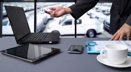 stock car: bussiness man working in office with  New Cars in Stock. Car Dealership Cars For Sale background Stock Photo