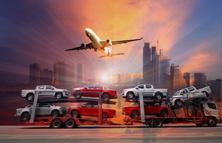 semitruck: The trailer transports  new cars on highway with big city background use for transportation industry or automotive industry