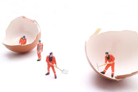 미니어처 작업자의 선택적 포커스 아이디어 개념에 대 한 계란, 흰색 배경 작업 사람들. 스톡 콘텐츠