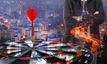 winner man: target dart with arrow with Double exposure of success businessman  ,metaphor to target marketing or target arrow concept. Stock Photo