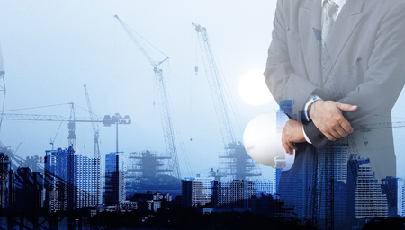 headman: Engineer or Safety officer holding hard hat with the mobile crane machine is background in construction site.
