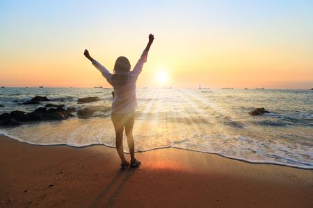 선셋 비치에서 응원 자유 경력이있는 여자. 무료 성공적인 느낌 바다를 보면서 위로 하늘에서 다시 팔에서 여성 성인에 성공 개념입니다. 그녀의 삶의  스톡 콘텐츠