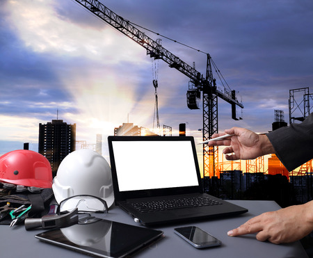 Industry 4.0 and Smart manufacturing concept. Laptop computer with Industrial 4.0 process diagram on screen against the industrial infrastructure background.