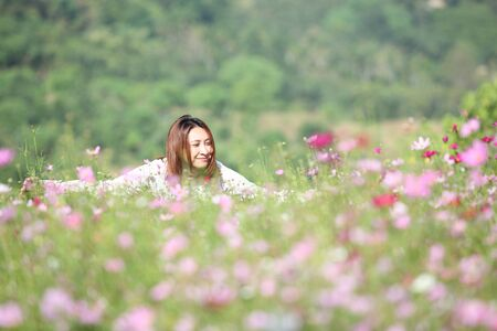Beautiful young woman in a field of Purple, pink, red, cosmos flowers in the garden with blue sky and clouds background in vintage style soft focus.