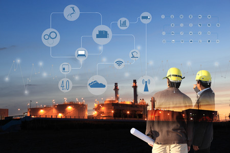automation: two engineer on site , Industry 4.0 concept image.Oil refinery at twilight with cyber and physical system icons diagram on industrial factory and infrastructure background.
