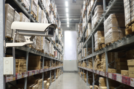 CCTV in interior of warehouse. Rows of shelves with boxes