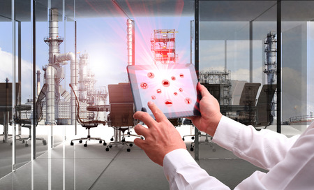 Industrie 4.0-concept .MAN hand die tablet met Augmented reality scherm en automatiseren draadloze Robotarm software in een industriële ruimte in slimme factory.Window tonen olieraffinaderij industrie achtergrond