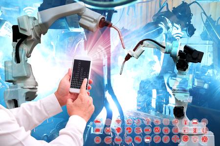인포 그래픽 Industry4.0 아이콘 스크린과 스마트 공장 배경 자동화 무선 로봇 팔의 블루 톤으로 핸드폰을 들고 가지 개념 .Man 손의 산업 인터넷