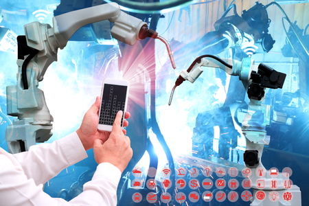 Industrial internet of things concept .Man hand holding cellphone with Infographic Industry4.0 icons screen and blue tone of automate wireless Robot arm in smart factory background Stockfoto