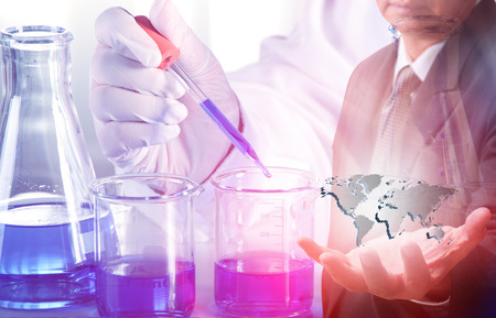 Flask in scientist hand with dropping liquid to test tube