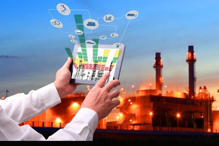 Industry 4.0 concept .Man hand holding tablet with Augmented reality screen and automate wireless Robot arm software at industrial room in smart factory.Window showing oil refinery industry background Reklamní fotografie - 71186513