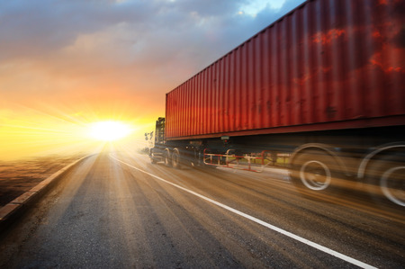 一般的な大型のトラックをアット サンセット - 高速道路上で高速輸送業界のコンセプトは、大きなトラックのコンテナー