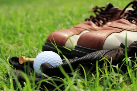 Golf ball and shoe on green grass