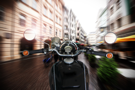 rejas de hierro: Man riding motorcycle. Rider driving motorcycle on a rural road in old town