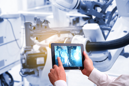 산업 4.0의 개념 인간의 손에 들고 Augmented 현실 스크린 소프트웨어와 블루 톤 자동 무선 로봇 공장 스마트 공장 백그라운드에서 태블릿. 혼합 매체