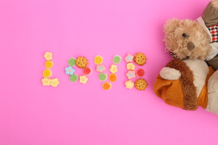 teddy bear with candy on pink background