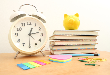 back in an hour: Book and alarm clock on wood desk.