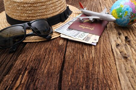 Go on an adventure! The world map and the passport and money on a wooden table. Top view. Stock Photo
