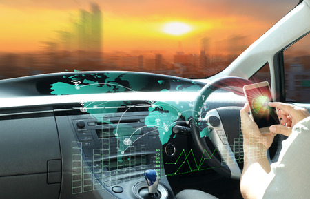 남자 사용하는 휴대 전화 지능형 자동차 또는 미래의 차량 및 그래픽 사용자 인터페이스 연결 된 자동차에 연결합니다. 사물의 인터넷. 헤드 업 디스플레이 (HUD). 스톡 콘텐츠 - 86679367