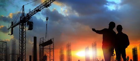 dwóch inżynierów na placu budowy, inżyniera i żurawie wieżowe na placu budowy i w tle miasta