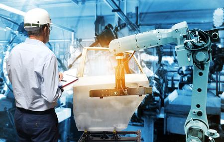 Mano de hombre sosteniendo control de calidad con brazo robot inalámbrico automatizado en fondo de fábrica inteligente. Medios mixtos de robot de soldadura en la industria de piezas de automoción