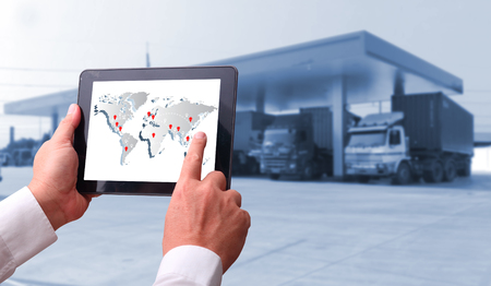 transportation import export concept,Man hand holding cell phone or tablet  automate wireless for control drlivery shipment