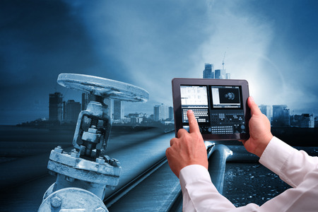 Industry 4.0 concept , Man hand holding tablet or cell phone  Augmented reality screen software and blue tone of automate wireless  pipelines Foto de archivo - 116898288