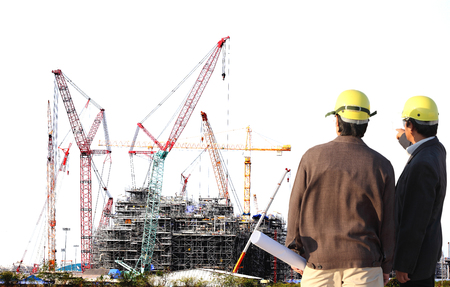 Chemical plant under construction with big crane with engineer working on site