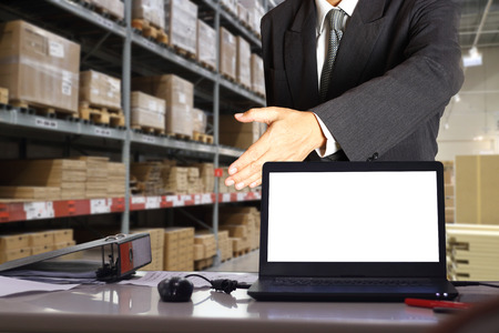 businessman in warehouse,he is standing at office of warehouse , he is planning management smart logistic concept