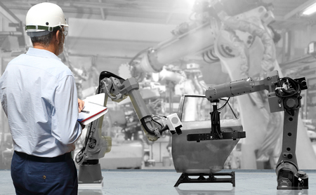 Man hand holding mobile phone or tablet with automate wireless Robot arm in smart factory background. Mixed media of welding robot in the automotive parts industry