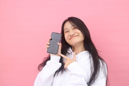 happy excited glad to receive text message informing about salary, rejoices good news, stares at mobile phone, actively from happiness, Beautiful Asian models over pink background for advertising concept