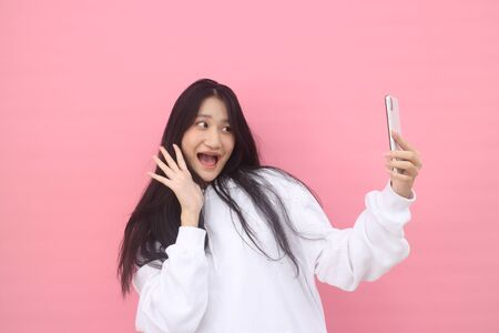 happy excited  glad to receive text message informing about salary, rejoices good news, stares at mobile phone, actively from happiness, Beautiful Asian models over  pink  background for advertising concept Foto de archivo