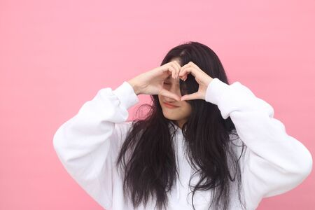 Portrait of beautiful long hair Asian woman with freckled face, shows heart gesture over chest, express love to close person, Beautiful Asian models over pink  background for advertising concept