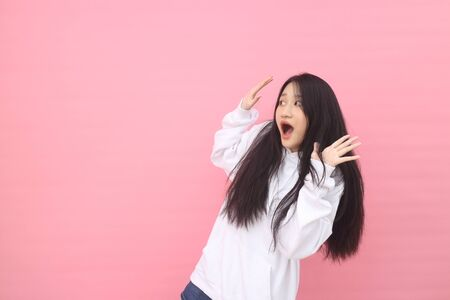 Isolated shot of pretty adult with long hair, broad smile, wears casual outfit, being entertained by friend during party, tilts head and looks with joy, dressed casually, Beautiful Asian models over pink  background for advertising concept 版權商用圖片