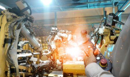 Mannhand, die Steuerung mit automatisiertem drahtlosem Roboterarm im intelligenten Fabrikhintergrund hält. Mischtechnik von Schweißrobotern in der Automobilteileindustrie