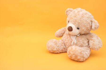 Teddy bear on yellow background Imagens