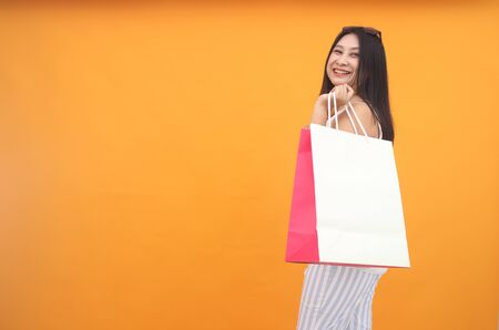 Isolated shot of pretty adult woman with shopping bag, wears casual outfit, dressed casually, Beautiful Asian models over yellow  background for advertising concept Imagens