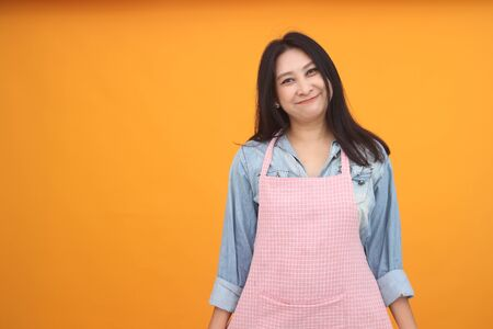 Happy Asian woman is cooking with apron for cooking advertise theme on on yellow background.