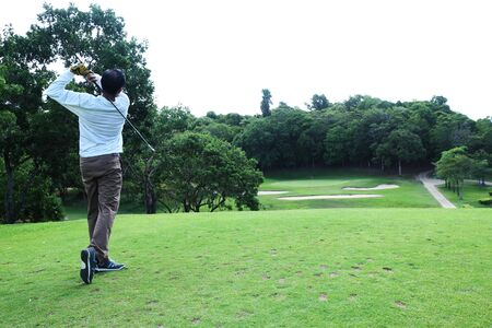 Asian golfer hit a golf ball by golf-club driver at golf course Imagens