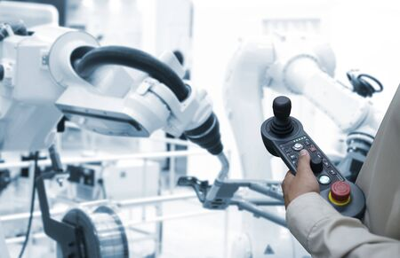 Man hand holding tablet or controller   with automate wireless Robot arm in smart factory background. Mixed media of welding robot in the automotive parts industry