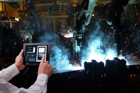 Industrie 4.0, Konzept der Hand des Mannes, die Tablet mit Augmented-Reality-Bildschirmsoftware und blauem Ton des automatisierten drahtlosen Roboterarms im Hintergrund der intelligenten Fabrik hält. Gemischte Medien Standard-Bild