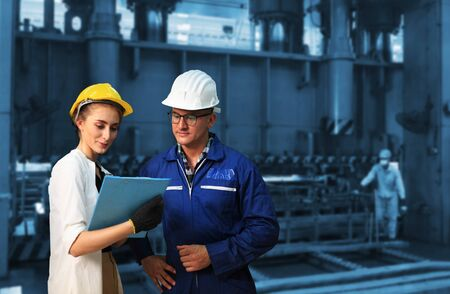 Industrial Engineers in Hard Hats  with  machine. Assist production engineer in industry.they checking metalwork control in industrial  factory
